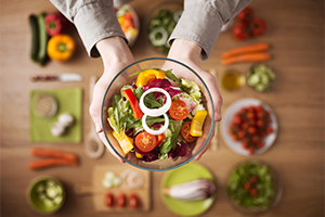 top down view of a woman's hands holding up a bowl of salad with other plates of vegetables defocused on the table below