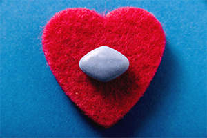 blue Viagra pill on a red heart