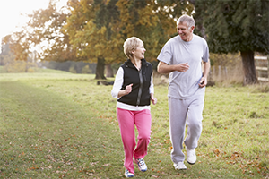 elderly couple in exercise clothes walking in the park