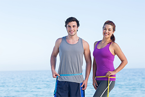 healthy fit couple standing with the sea in the background