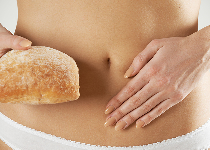 wheat intolerant woman holding bread showing her stomach
