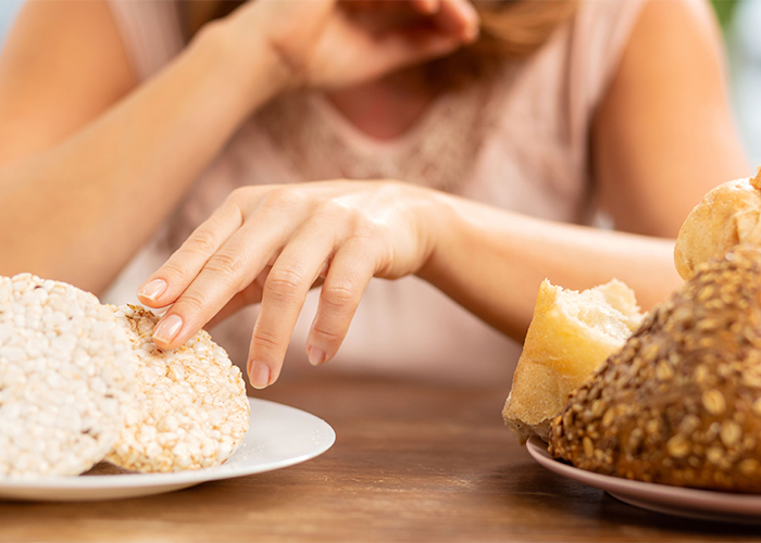 woman with gluten sensitivity choosing a rice cake instead of bread