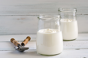 two jars of yoghurt on a white wooden table with two spoons next to them