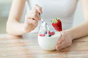 woman about to dig into a yogurt with fresh berries
