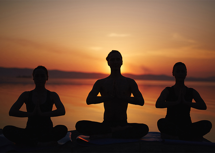 three people meditating at sunset